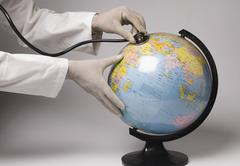Close-up of a person's hands examining a globe with a stethoscope - stock photo