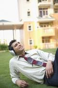 Businessman lying on the grass and listening to music Stock Photos