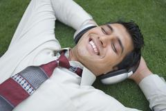 Businessman listening to music and smiling Stock Photos