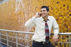 Businessman leaning against a railing and talking on a mobile phone Stock Photos