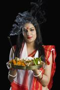 Stock Photo of Beautiful woman in a Bengali sari holding pooja thali