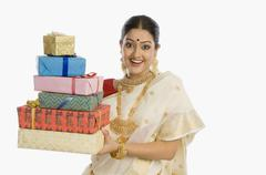 Portrait of a woman in traditional saree holding gifts and smiling - stock photo