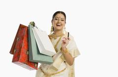 Woman in traditional South Indian sari holding shopping bags with a credit card - stock photo