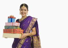 Stock Photo of Portrait of a woman in traditional Assamese dress holding gifts and smiling