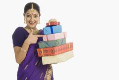 Stock Photo of Portrait of a beautiful woman in traditional Assamese dress holding gifts and