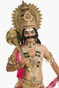 Portrait of a stage artist dressed-up as Ravana and holding a mace - stock photo