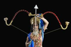Man dressed-up as Rama and holding a bow and arrow - stock photo