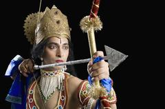 Stage artist dressed-up as Rama and holding a bow and arrow Stock Photos