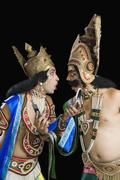Two men dressed-up as Rama and Ravana and reading text message Stock Photos