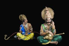 Two stage artists dressed-up as Rama and Ravana and talking on a mobile phone Stock Photos