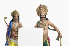 Two men dressed-up as Rama and Ravana and holding a blank placard Stock Photos