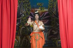 Stage artist dressed-up as Rama blessing and holding a conch shell Stock Photos