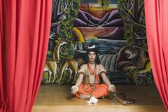 Stage artist dressed-up as Rama and praying - stock photo