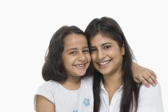 Woman hugging her daughter and smiling Stock Photos