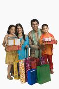 Family holding shopping bags and gifts for Diwali - stock photo