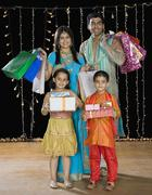 Family carrying shopping bags and gifts for Diwali Stock Photos
