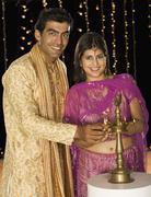 Couple lighting oil lamp on Diwali festival - stock photo