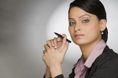 Close-up of a businesswoman holding a pen - stock photo
