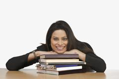 Stock Photo of Portrait of a businesswoman resting her face on books and smiling