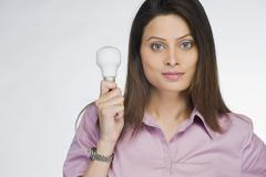 Businesswoman holding a light bulb - stock photo