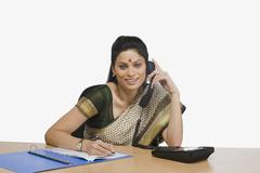 Businesswoman talking on the telephone in an office Stock Photos