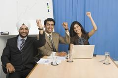 Business executives raising hands in an office Stock Photos