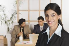 Stock Photo of Businesswoman smiling with her colleagues in the background
