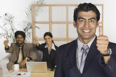 Business executives showing thumbs up sign Stock Photos