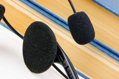 Stock Photo of headphones with a microphone and a stack of books isolated on white backgroun