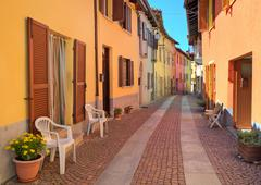 Narrow cobbled street among colorful houses in italy. Stock Photos