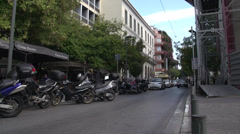 Athens, traffic down narrow street, motorbikes parked Stock Footage