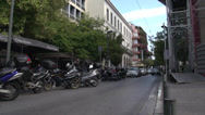 Stock Video Footage of Athens, traffic down narrow street, motorbikes parked