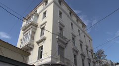 Athens apartment and traffic on narrow street, tilt down reveal Stock Footage