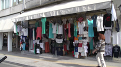 Athens, woman walks past clothes shop Stock Footage