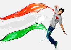 Tricolor paints being splashed on a man Stock Photos