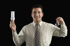 Businessman comparing a light bulb with an energy efficient lightbulb - stock photo