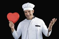 Stock Photo of Portrait of a chef holding a heart shape gift