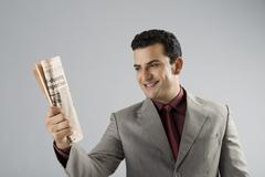 Businessman holding a newspaper - stock photo