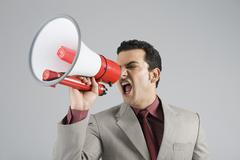Businessman shouting into a megaphone - stock photo