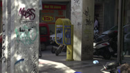 Stock Video Footage of Athens gritty street corner, people and traffic, graffiti covers pillars
