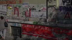Athens, gritty street plastered ads and graffiti people walk by Stock Footage