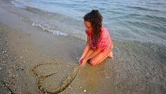 Beautiful teen on the beach drawing a heart deleted by sea - Stock Video. Stock Footage