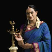 Stock Photo of South Indian woman lighting an oil lamp