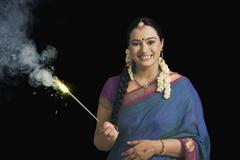 Woman celebrating Diwali festival with a sparkler - stock photo