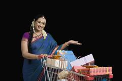 Woman carrying Diwali gifts in a shopping cart - stock photo