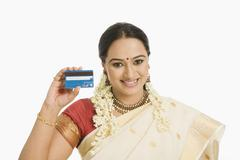 Stock Photo of Woman showing a credit card and smiling