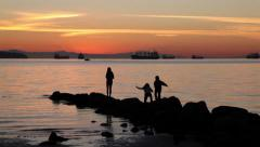 Sunset in Vancouver with kids on the rock at English Bay Stock Footage