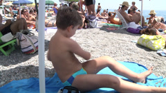 Boy on the bach under umbrella. Stock Footage
