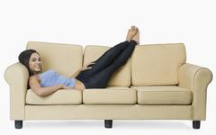 Woman resting on a couch and smiling - stock photo