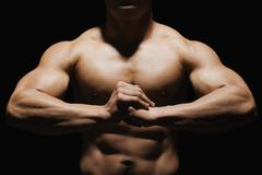 Close-up of a muscular man showing his muscles - stock photo